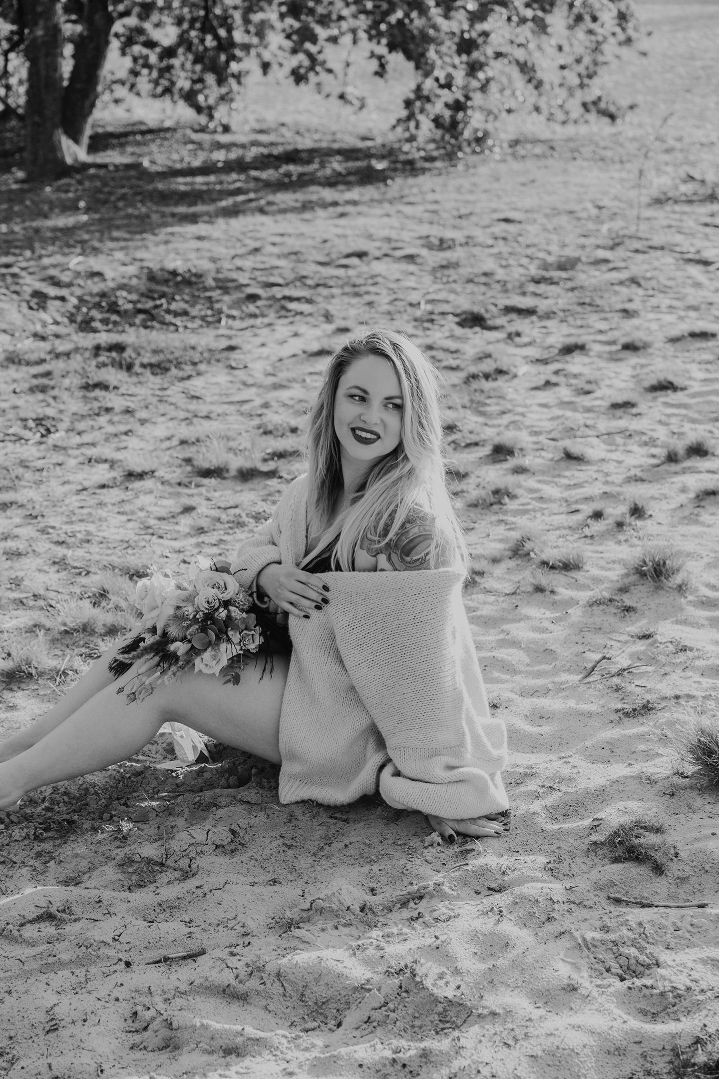 Schwarz-Weiß-Aufnahme einer schönen Frau mit Blumen auf dem Schoß
