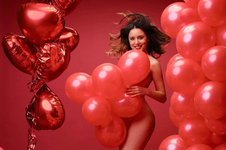 Schöne Frau, die mit roten Ballons für sinnliche Fotos posiert.