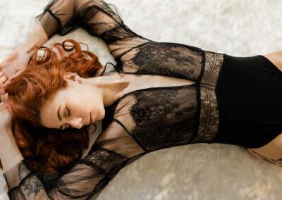 Rothaarige Schönheit liegt auf dem Boden in schwarzem Body für sinnliche Bilder