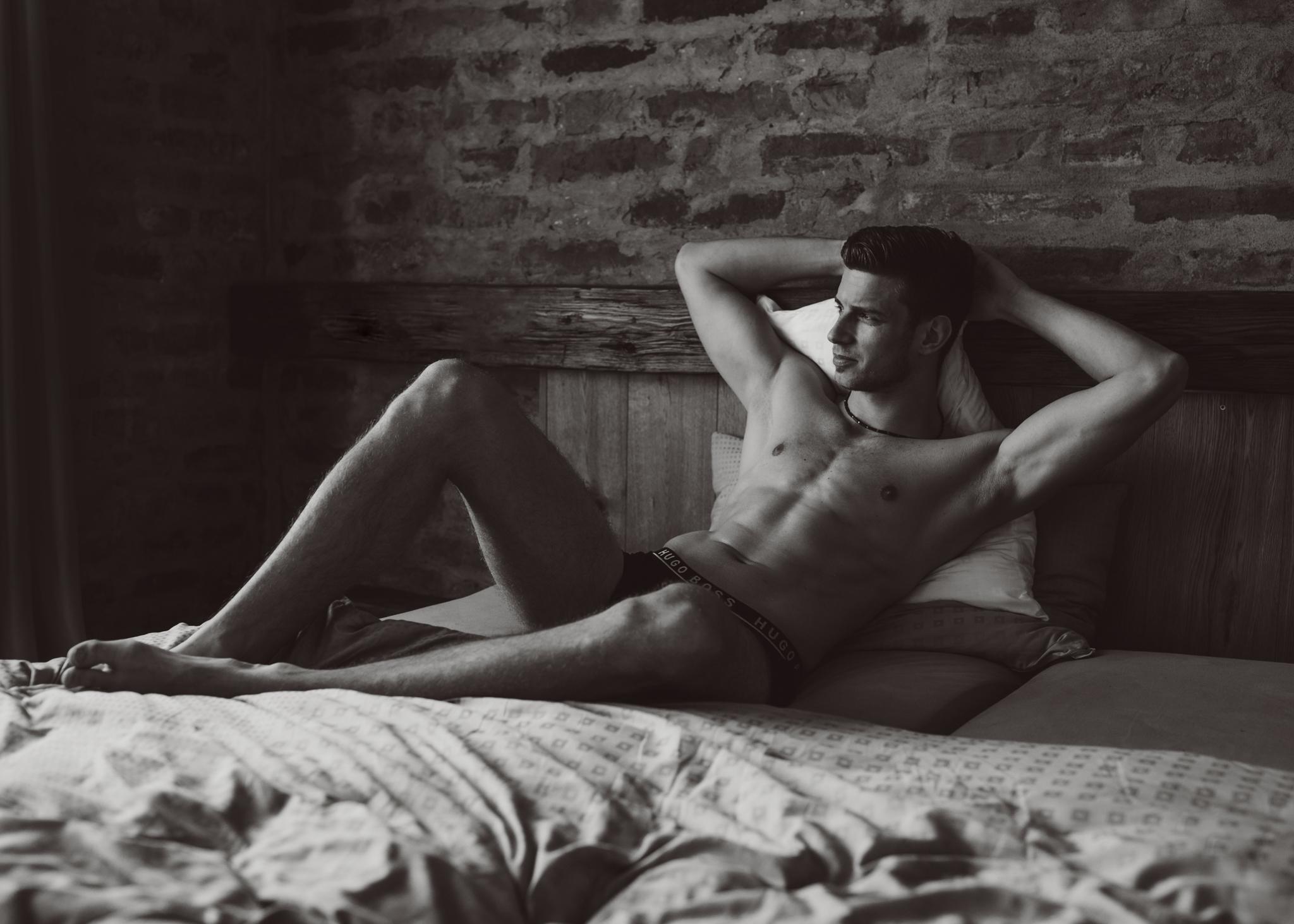 Boudoir-Shooting mit einem Mann auf dem Bett in klassischem Schwarz-Weiß