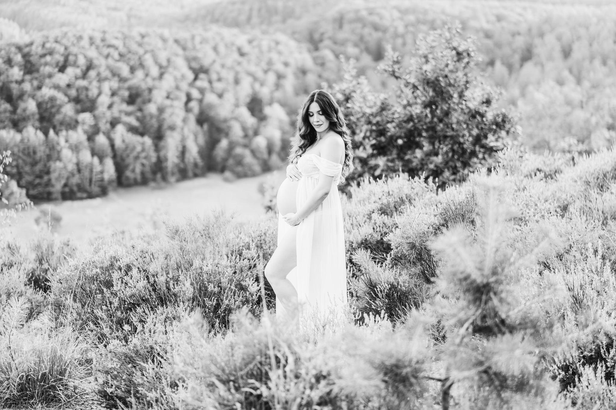 Frau sitzt auf einer Düne und lächelt