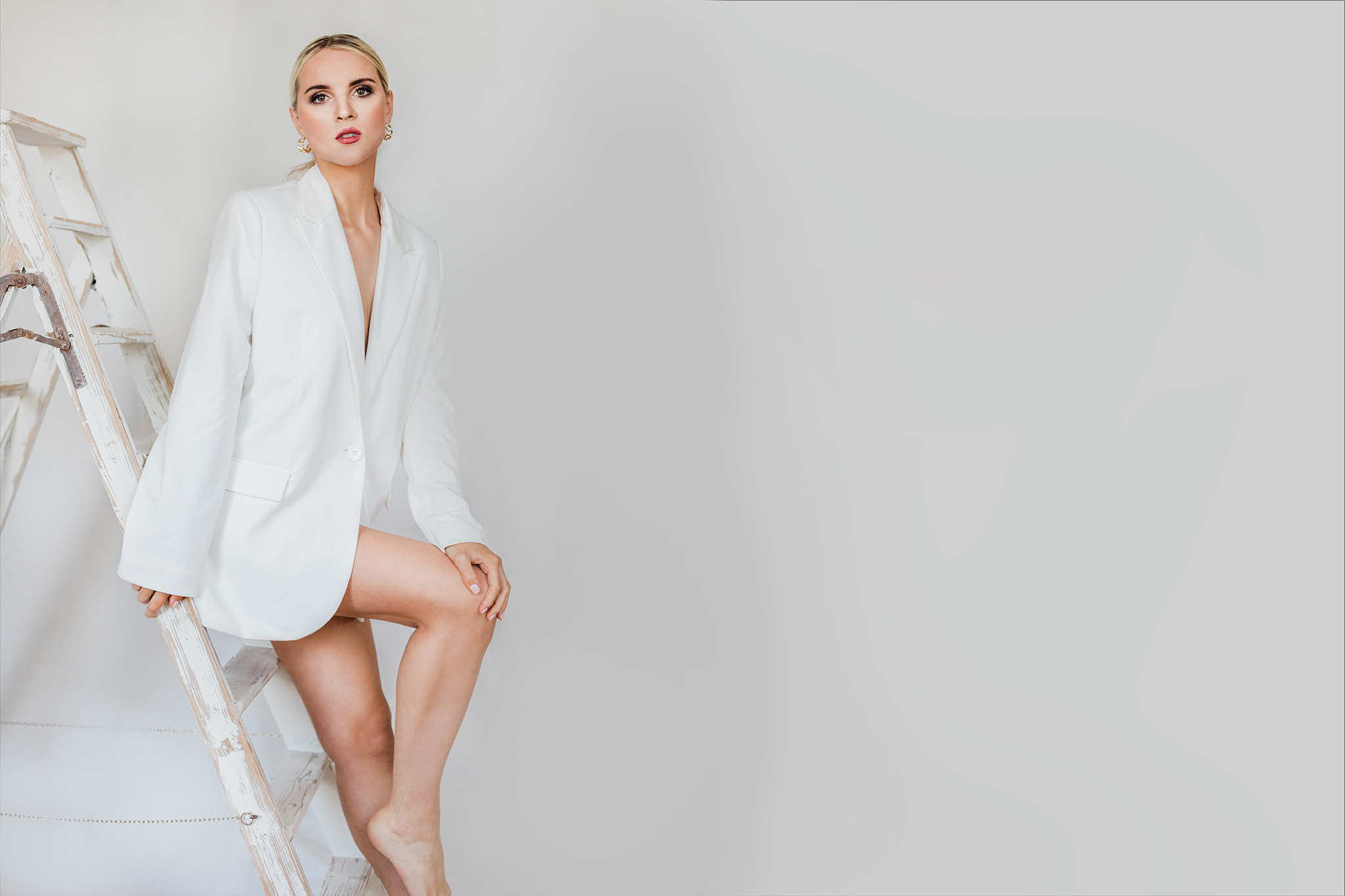 Blonde Frau sitzend bei ihrem Boudoir-Fotoshooting im Editorial Look mit weißem Long Blazer